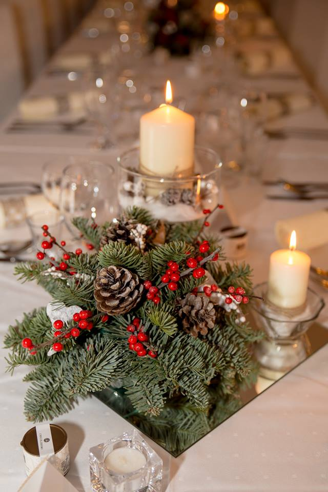 dekorácia zo živej čečiny v zimnom štýle doplnená šiškou a červenými plodmi na zrkadlovom podmose a sviečkami