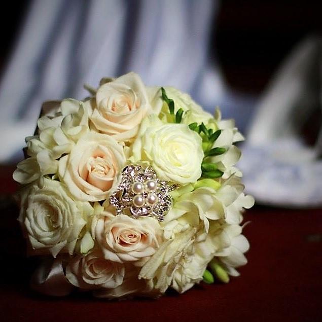 smotanové ruže a biele frézie ako svadobná kytica s perlovou brošňou
