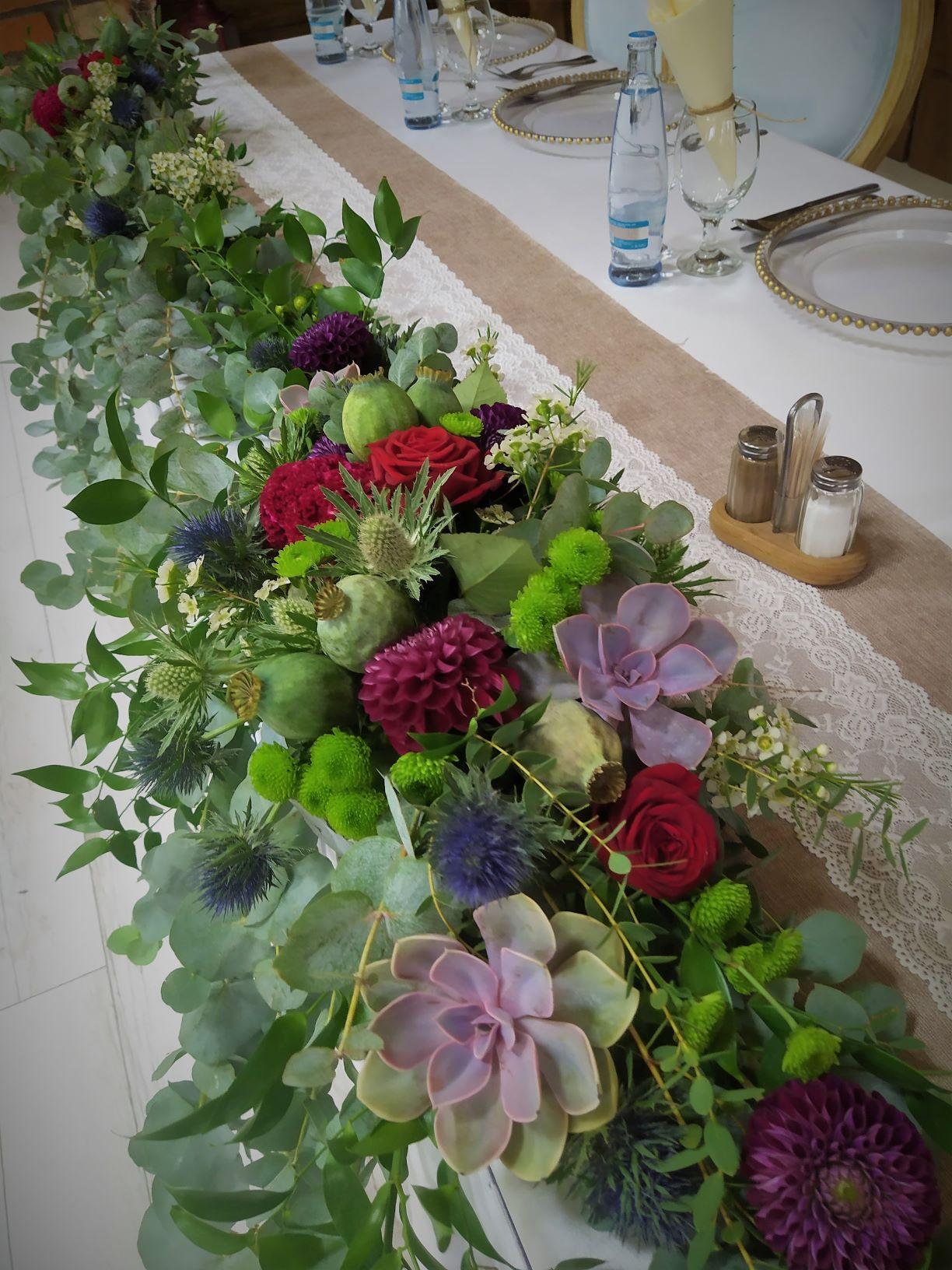 kvetinova dekoracia na kraj stola po celej dlžke zelono bordova ruže, eukaliptus,makovice, bodliaky