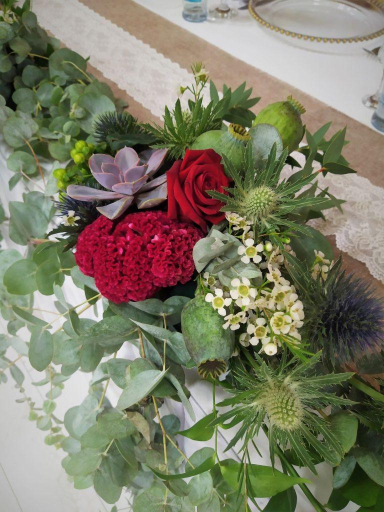 kvetinova dekorácia v eukaliptusovom zaklade s bordovymi ruzami,bodliakmi