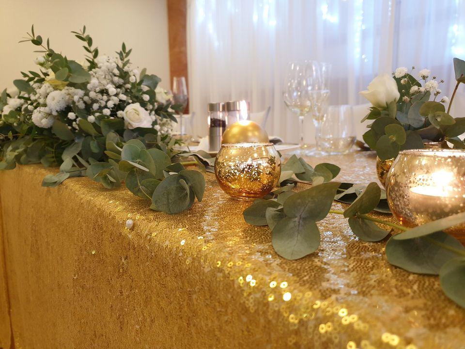 zlatý obrus na stole pre mladomanželov s eukaliptusovou výzdobou a sviečkami
