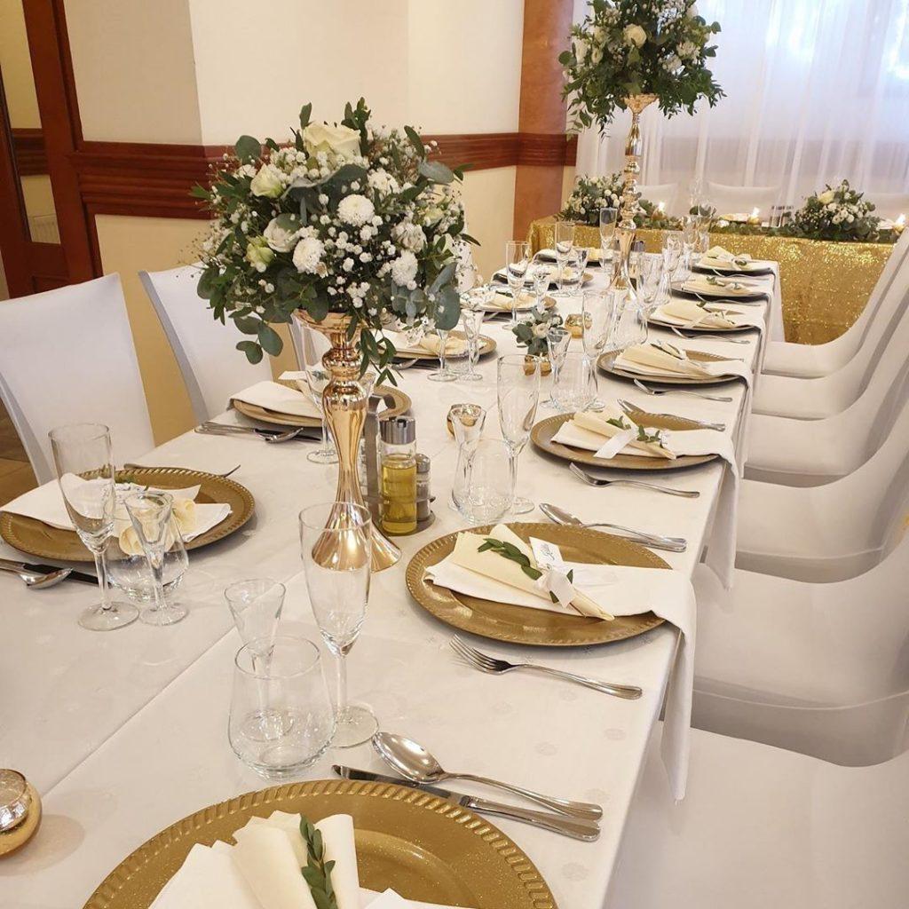 svadobna vyzdoba, na zlatych svietnikoch kvetinove dekorácia z eukaliptusu a bielych kveti, zlate klubove taniere