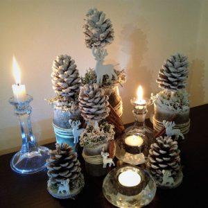 Horiace sviečky v sklenených svietnikoch, stromčeky zo zasnežených šišiek.