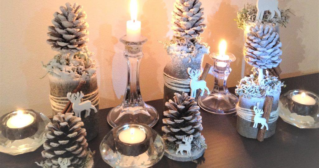 zátišie so sviečkami a zasneženými šiškovými stromčekmi, dekorovanie s deťmi