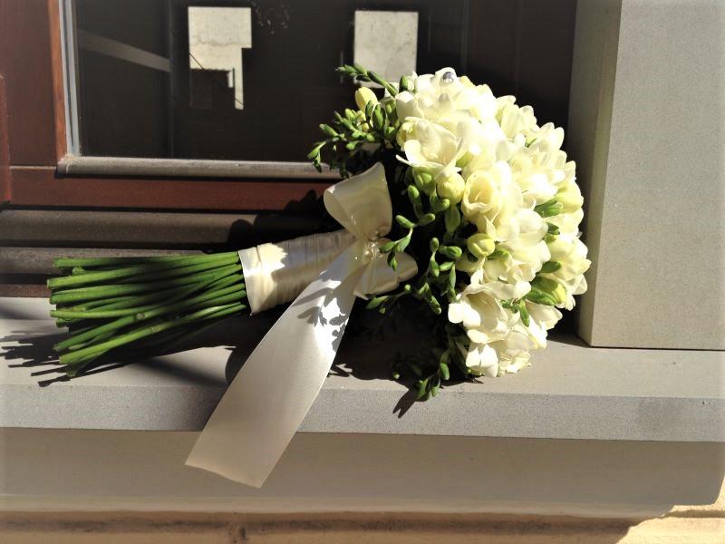 okrúhla svadobná kytic z bielych frézií previazaná bielou stuhou a mašličkou