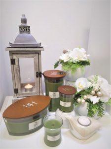 darčeky, zelené wood wick sviečky, sivý lampáš, dekorácia v bielom kvetináči s orchydeou
