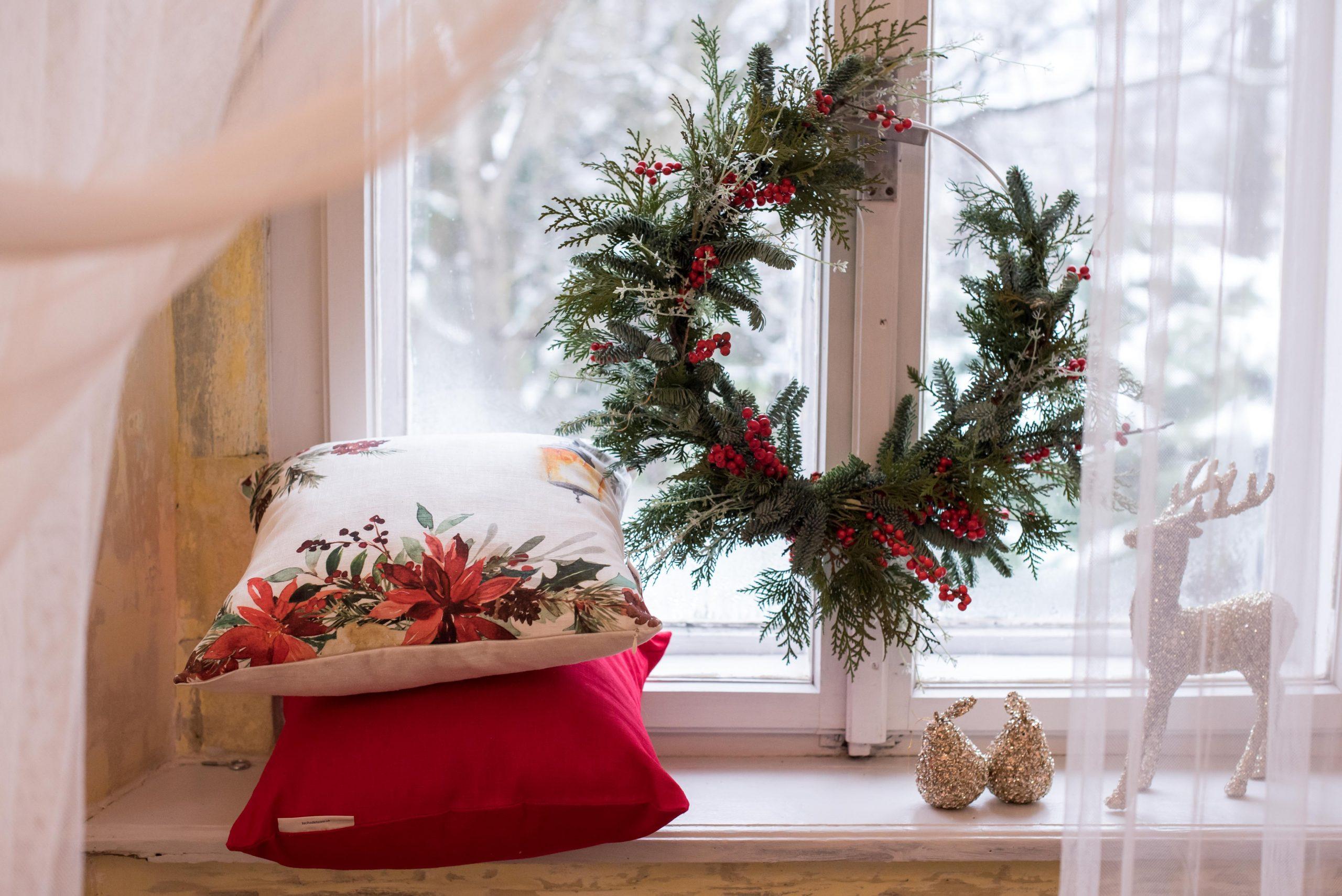 Vianočná atmosfére,čečinový veniec zavesený v okne,na parapete poukladané vianočné vankúše a ozdoby