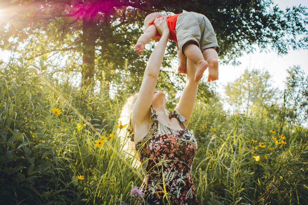 matka s dieťaťom v rukách na lúke, deň matiek