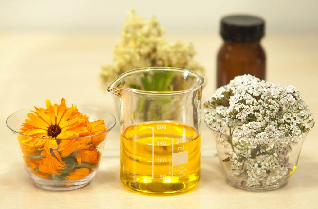 slnečnicový olej v skle s bylinkami vo vedľajších miskách